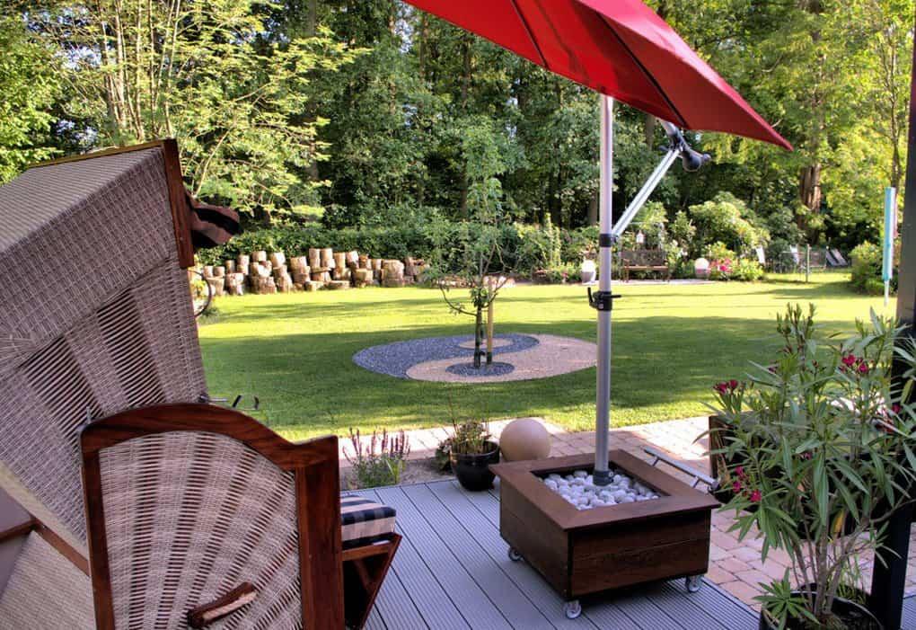 HERSAND GmbH Schirmstaender mit rotem Schirm im Garten mit Strandkorb