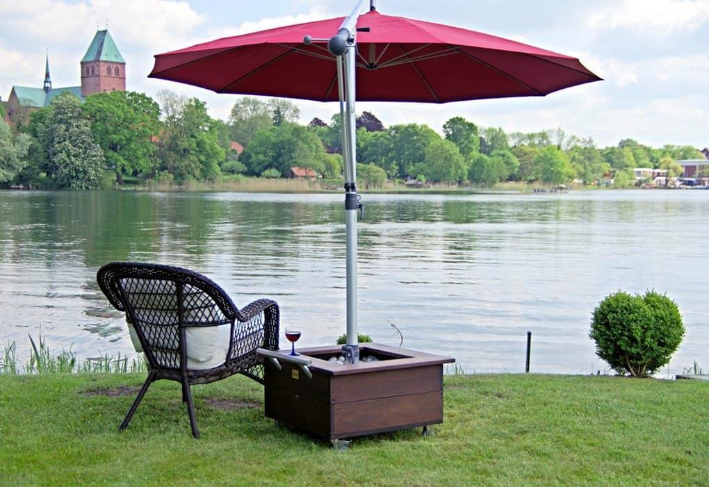HERSAND GmbH roter Sonnenschirm mit Stuhl am Wasser