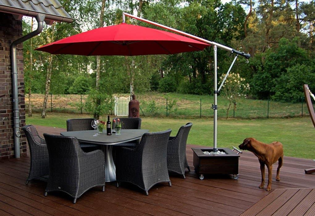 HERSAND GmbH roter Sonnenschirmstaender auf Terrasse mit Tisch und Hund